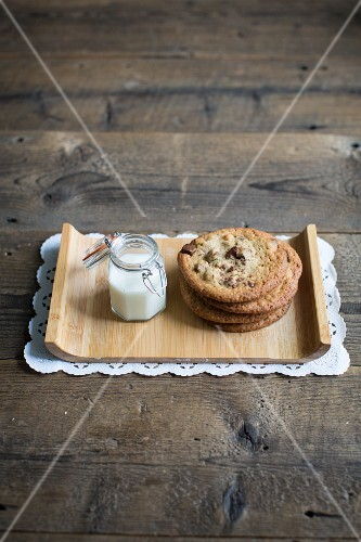 Chocolate chip cookies and milk on a wooden tray