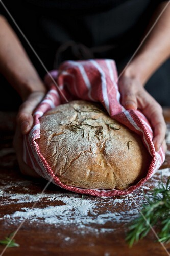 Hands holding a freshly baked loaf of bread in a tea towel