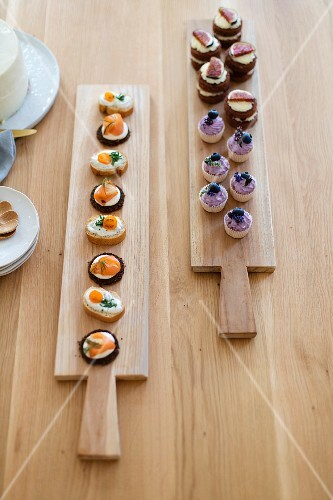 Various canapés on long wooden boards