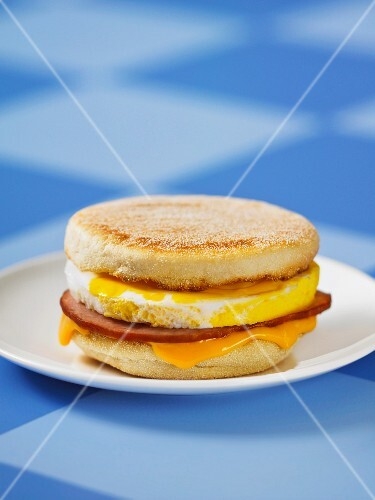 An English muffin with Canadian bacon and Cheddar cheese