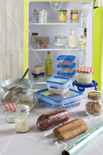 Sausage and cheese stored in plastic containers and glass jars