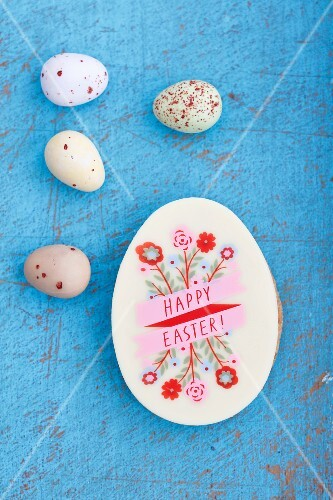 An egg-shaped Easter biscuit decorated with writing and sugar quail's eggs