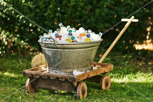 A zinc bathtub filled with chilled drinks for a garden party