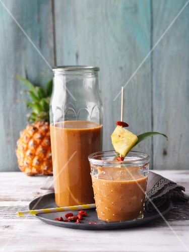 Pineapple and gojiberry smoothies with bananas, coconut mousse and maca