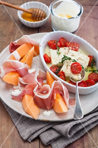 Honeydew melon with ham, gratinated feta cheese with cherry tomatoes and honey yoghurt