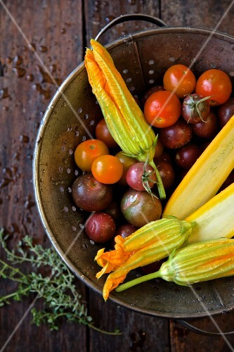 Heirloom tomatoes, yellow courgettes and courgette flowers in a colander