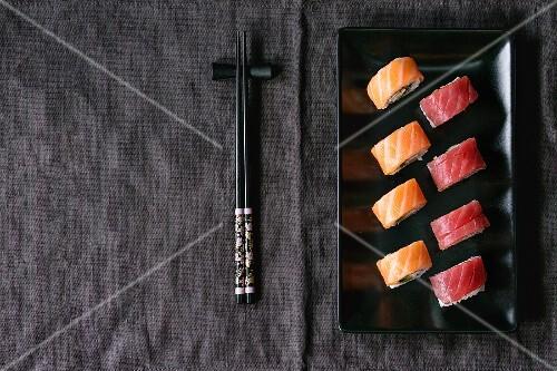 sushi mit lachs und thunfisch auf schwarzem teller daneben essst bchen japan bild kaufen. Black Bedroom Furniture Sets. Home Design Ideas