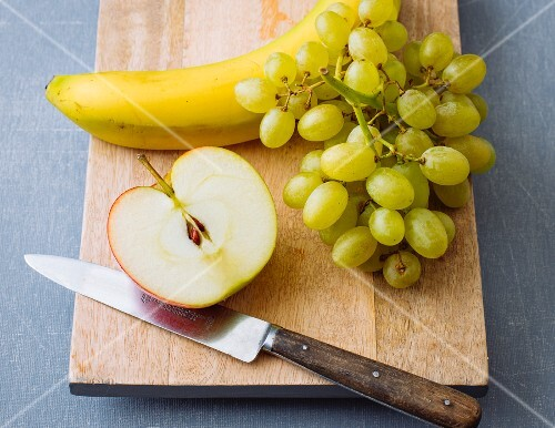 Half an apple, banana and grapes