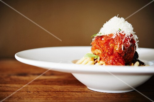 A spicy meatball with tomato sauce and grated cheese on pasta