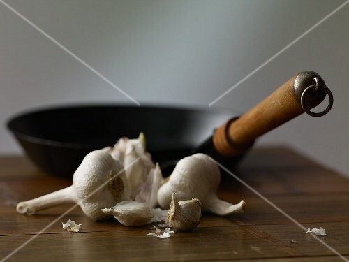 Garlic and a pan on a wooden table