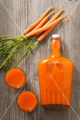 Carrot juice in glasses and a flip-top bottle (seen from above)
