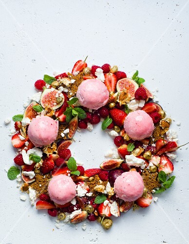 A Christmas wreath dessert with gingerbread stars, fruit and ice cream