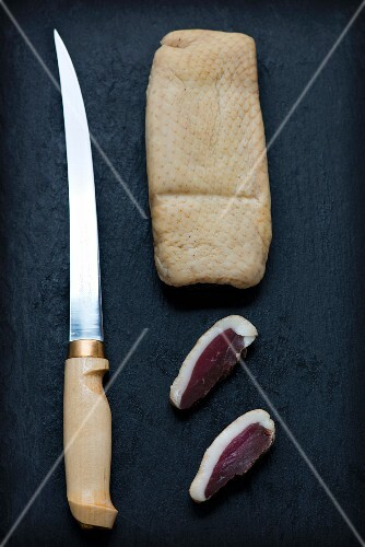 Smoked preserved duck breast with slices cut off next to a flitting knife