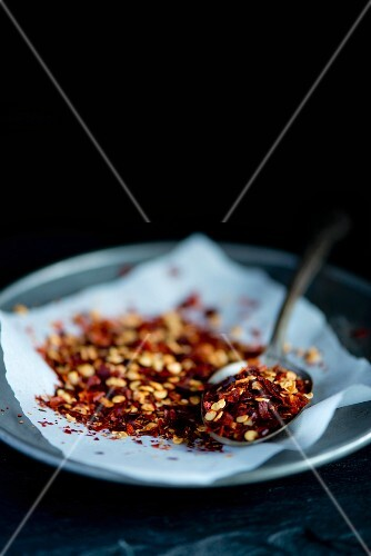 Red Italian chilli flakes on a pewter plate on a white piece of paper