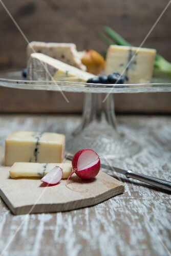 Jacobean sage, Cambozola, Morbier and Wensleydale on a glass stand with radishes and Morbier on a wooden board