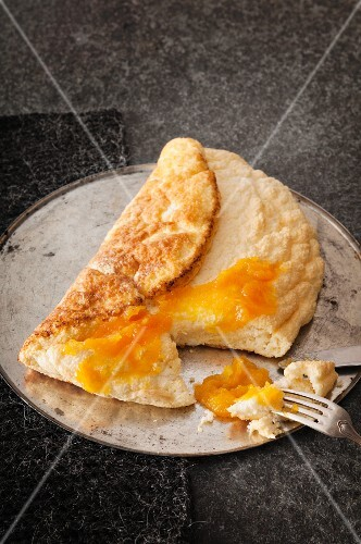 A sponge omelette on a round baking tray with pumpkin and orange marmalade, sliced