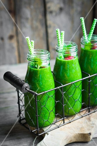Green smoothies and small glass bottles garnished with raspberries
