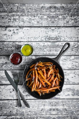 Sweet potato fries in cast iron pan on a rustic wooden surface