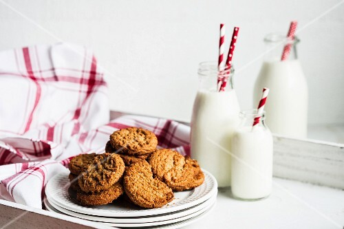Oatmeal cookies and bottles of milk on a white wooden tray