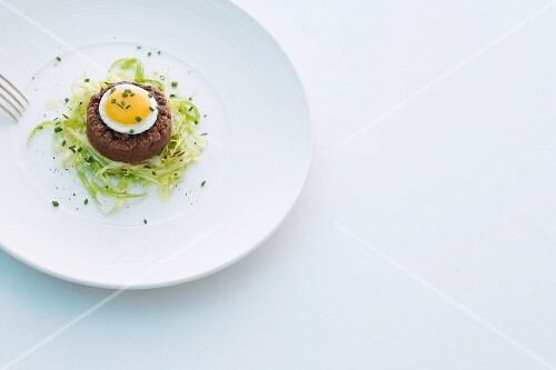 Fried beef tartare with fried quail's egg on a bed of pointed cabbage