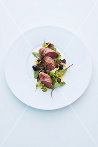 Wild rabbit wrapped in bacon on a mixed leaf salad with blackberries