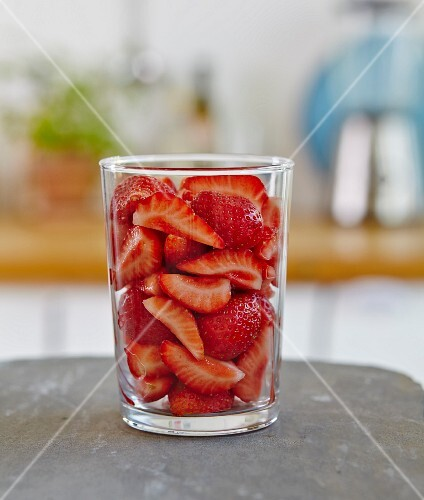 A glass of sliced strawberries