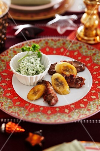 Beef wrapped in bacon with a herb sauce and fried plantains