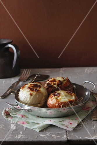 Stuffed onions with cheese in a pan