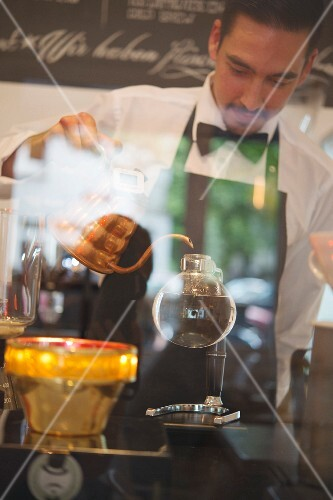 Filter coffee being made, a barista with a syphon in the 'Stockholm Espresso Club' in Hamburg