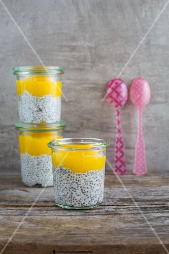 Three glasses of chia and coconut pudding with mango mousse