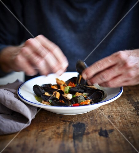 A person eating mussels