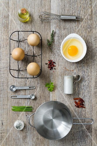 An arrangement of kitchen utensils and ingredients for egg dishes (seen from above)