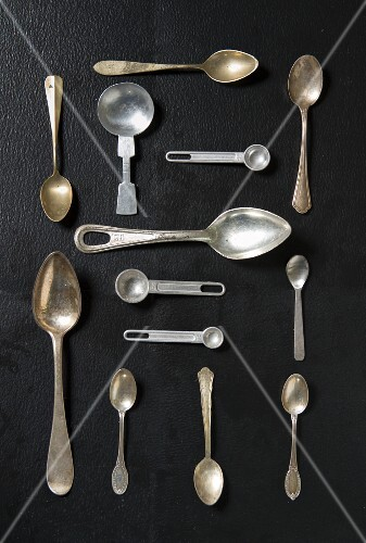 An arrangement of various spoons on a black surface