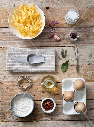 Fresh tagliatelle with ingredients on a wooden surface