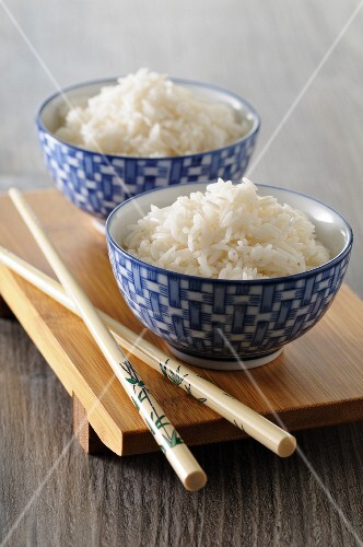 Cooked rice in Oriental bowls with chopsticks