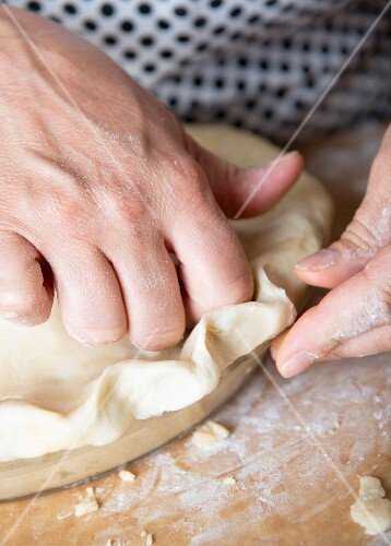 Doublecrossed pie being made: pastry lid being pushed down by hand