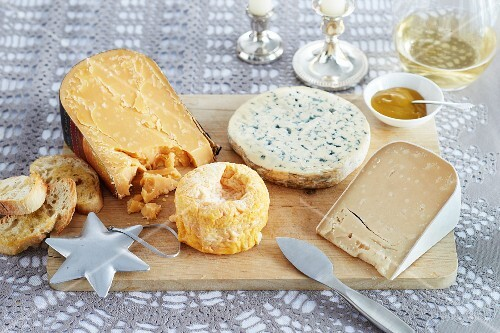 Various types of cheeses and bread on a cheese board