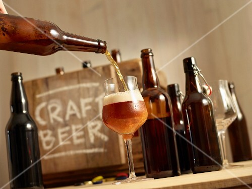 Beer being poured with open bottles of beer and a wooden crate labelled 'Craft Beer' in the background