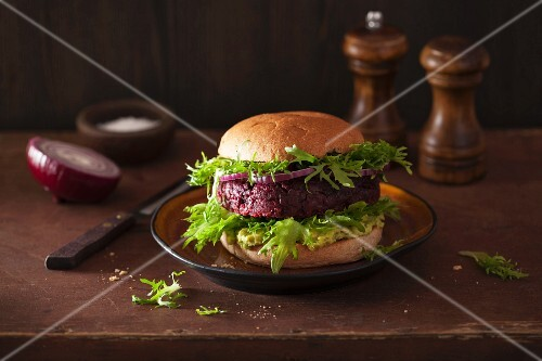 A veggie burger with a beetroot patty and avocado spread