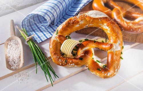 Lye bread pretzels with butter and chives next to a scoop of salt and a bundle of chives on a white wooden surface