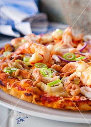 Pizza with seafood, olives and spring onions (detail)