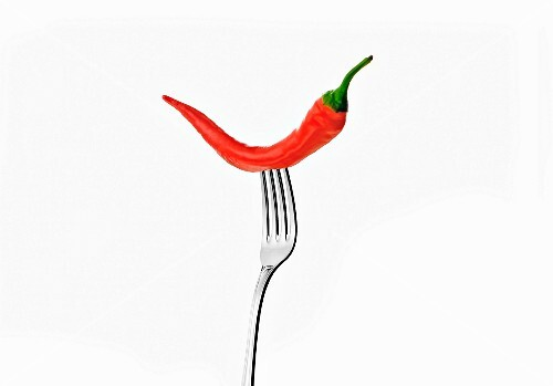 A chilli pepper on a fork against a white background