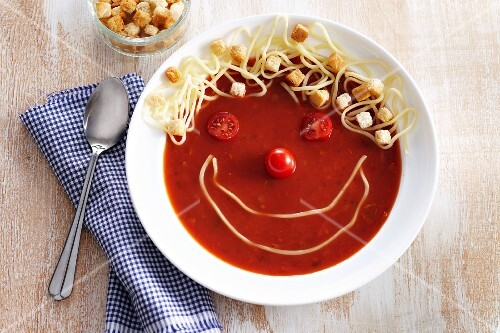 Funny tomato soup with cheese strings and croutons