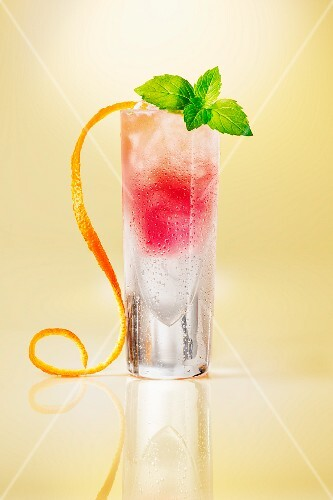 Pink cocktail glass garnished with orange zest on a yellow surface