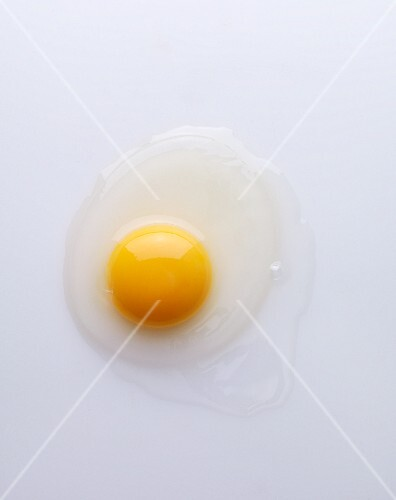 A freshly cracked egg on a white surface