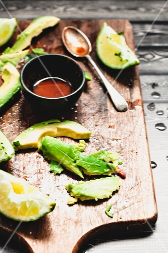 Avocadoes and limes on a chopping board with a bowl of chilli olive oil