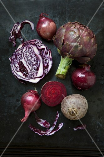 An arrangement of vegetables featuring artichokes, red onions, red cabbage and beetroot