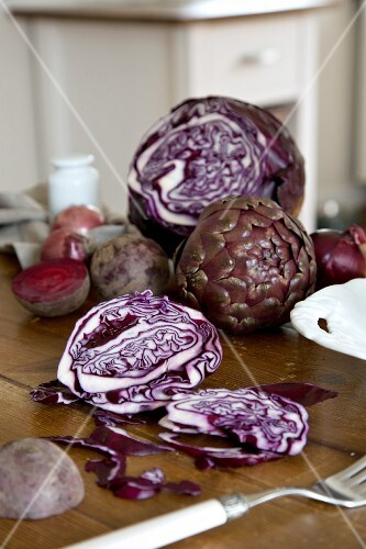 An arrangement of vegetables featuring artichokes, beetroot and red cabbage on a kitchen table
