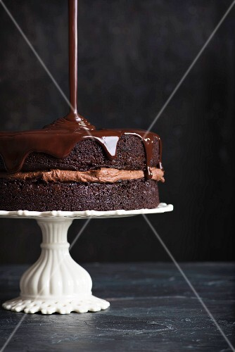 Chocolate glaze being poured over a chocolate cake