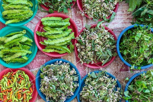 Edible flowers and goa beans on a market stand in Vientiane, Laos EN